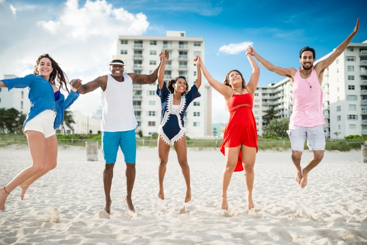 Five people jumping into the air smiling at the beach